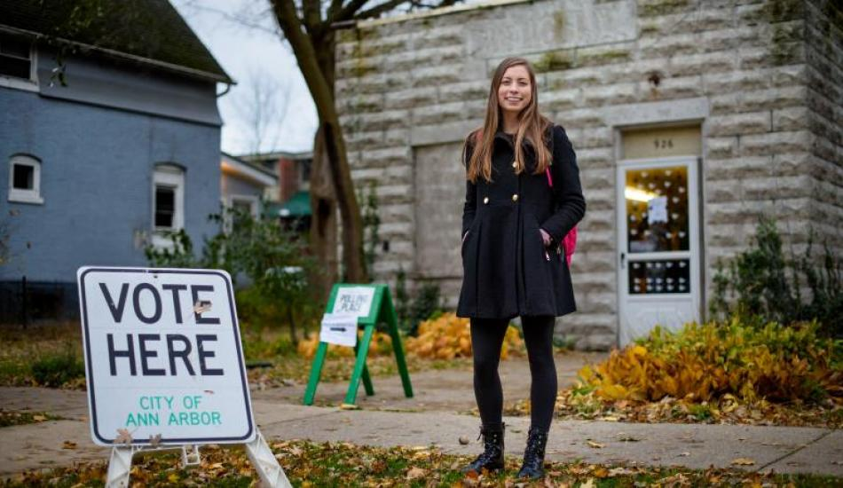 "Shaelyn Albrecht standing in front of a polling location, there is a sign that says ""vote here"" to her right."