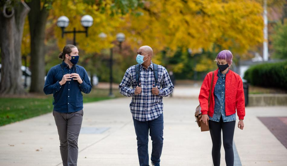 Three students walking on the University of Michigan campus and wearing masks