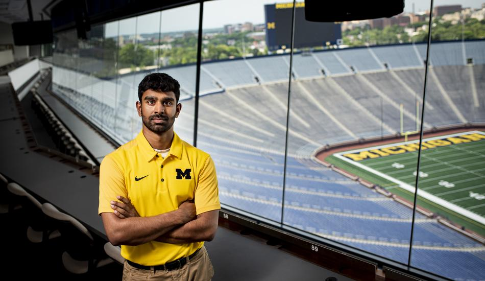 Rohit Mogalayapalli in a box in the big house. The field and bleachers below are empty.  He is wearing a Maize polo.