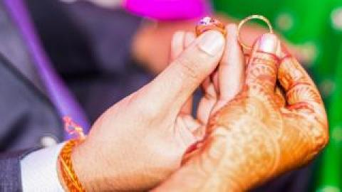 The hands of a bride and groom holding rings. The bride's hand is adorned with intricate henna.