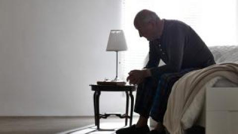 An elderly man sitting on the edge of the bed.