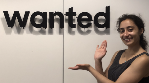 "Salma Siddiqui posing next to a sign displaying the ""wanted"" logo."