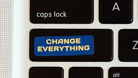 A laptop keyboard with a Change Everything sticker over the shift key