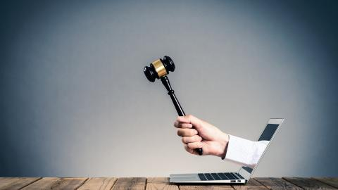 A hand holding a gavel coming out of a laptop screen