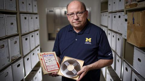 Paul Conway, a University of Michigan School of Information professor, holds a reel-to-reel tape with its matching broadcast script.