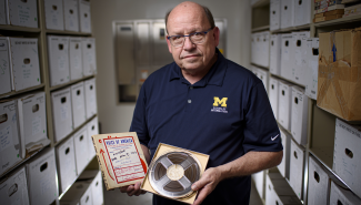 Paul Conway holds a reel-to-reel tape with its matching broadcast script.